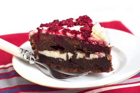 Raspberry chocolate layered cake with white butter cream, jam and berries on white background