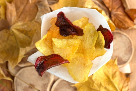 Potato and beet homemade chips in paper cone on natural wood background with autumn leaves. Stock Photo