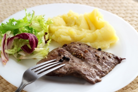 Fried steak with pepper, mashed potato and mixed salad on brown background with fork.