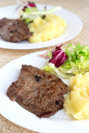 Fried steak with pepper, mashed potato and mixed salad on brown background.