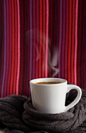 A white cup of very hot coffee on the background of scrafs. Stock Photo
