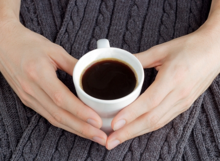serenety: A white cup of coffee in man heart shaped hands on the background ofthe grey scraf Stock Photo