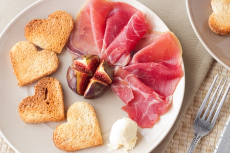 A starter with heart shaped toasts, grilled fig, ball of butter and hum. Pastel background, fork. Stock Photo
