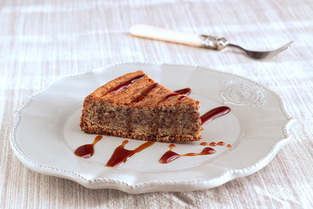 Chocolade and almond cake with caramel sauce, fork on vintage brown plate and on natural pastel napkin with sugar pieces. Horizontal.
