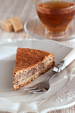 Chocolade and almond cake with caramel, fork and sweet tea in transparent cup. On vintage brown plate and on natural pastel napkin with sugar pieces. Vertical. Stock Photo