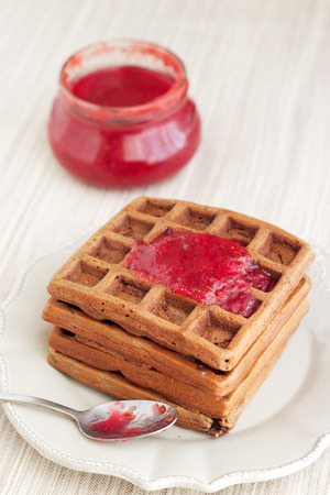A bunch of chocolate gold brown waffles on light pastel vintage plate and natural napkin. Decorated with red jam with a spoon. Stock Photo