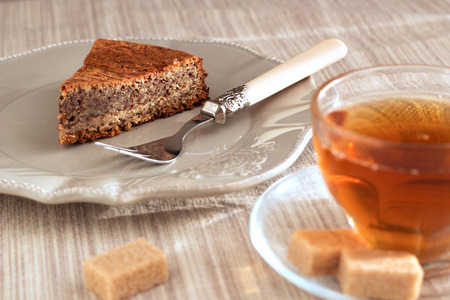 Chocolade and almond cake with caramel sauce, fork and sweet tea in transparent cup on the foreground. On vintage brown plate and on natural pastel napkin with sugar pieces. Horizontal.