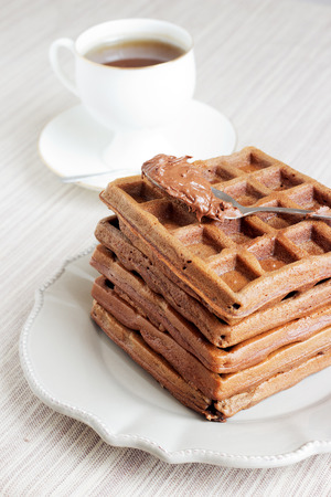 A bunch of chocolate gold brown waffles with a bite on light pastel vintage plate and natural napkin. Decorated with a tea spoon of melted chocolate, served with a white cup of tea.