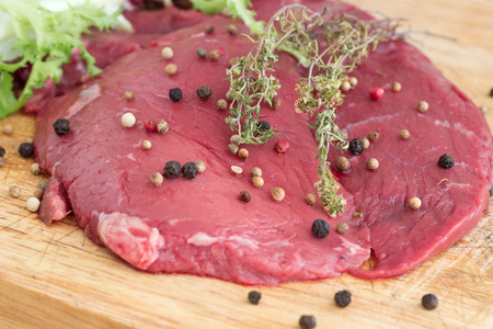 Freash raw red beef with peper mix and red berries on whooden background with green salad and thyme.