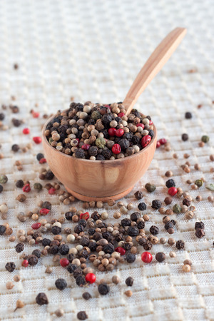A wood bowl of mixed pepper and red dry berries on brown background.
