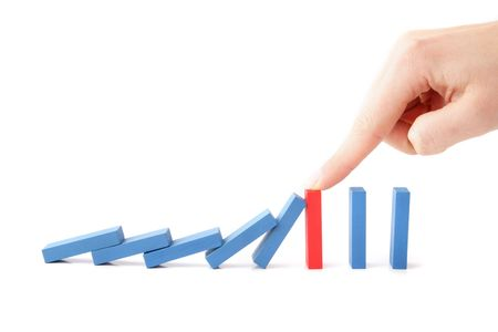 intervening: A human hand intervenes a chain reaction of a domino game. All isolated on white background.