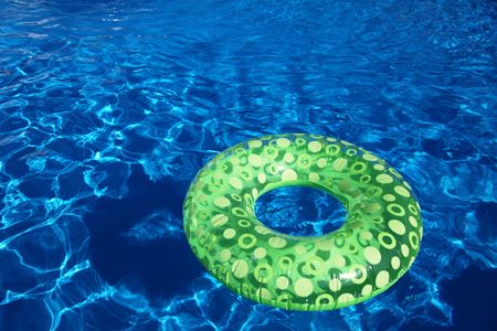An inflatable green plastic ring swimming in a shiny blue swimming pool. Stock Photo - 6186746