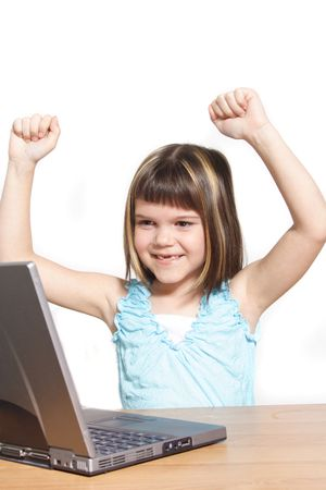 A young girl jubilating in front of her notebook computer. All isolated on white background. photo