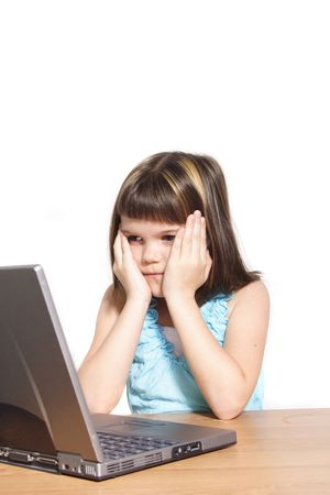 A young girl sitting in front of a broken notebook computer. All isolated on white background. photo