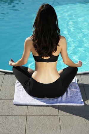 An attractive young woman doing yoga beside the swimming pool. photo