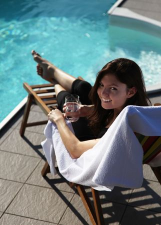 A very attractive young woman enjoying the sun while sitting in a deck chair next to a swimming pool. photo