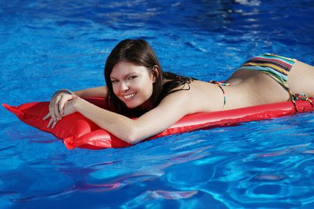 A very attractive young woman taking a sunbath on her red air mattress. photo