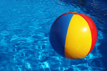 An inflatable colored plastic ball swimming in a shiny blue swimming pool. photo