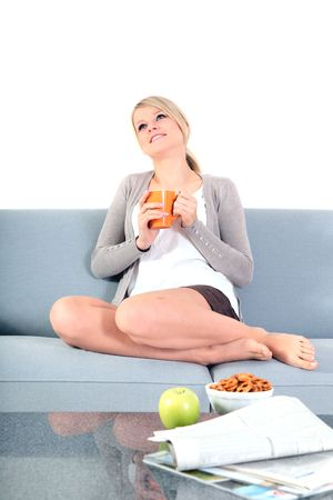 tea cosy: An attractive young woman enjoys a cup of coffee while sitting on a couch. Stock Photo