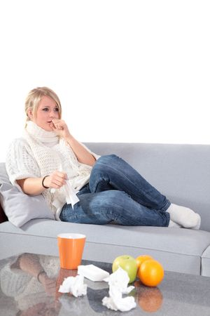 An attractive young woman feeling very bad while sitting at home on her couch. photo