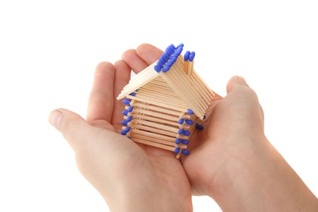 A human hand protecting a stylized house out of matchsticks. All isolated on white background. photo