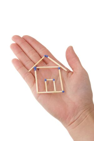 A human hand protecting a stylized house out of matchsticks. All isolated on white background. Фото со стока