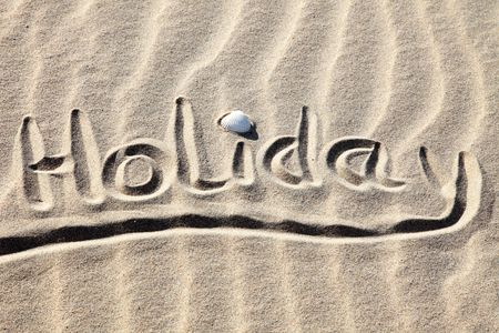 Holiday written in golden sand on a beach. Stock Photo - 6293714