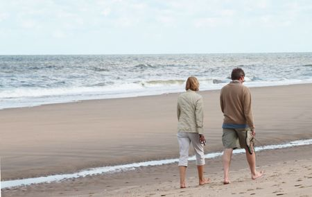 appealing attractive: Middle aged man and woman taking a walk on the beach.
