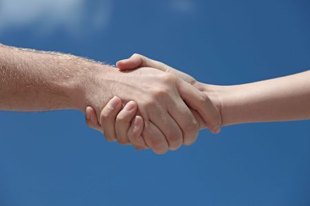 meet and greet: A man and woman handshaking in front of a bright blue sky.