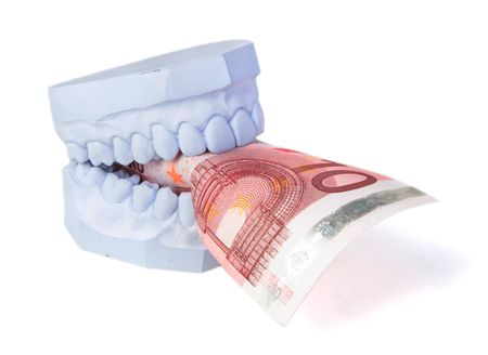 complementary: A set of teeth with some money. All isolated on white background.