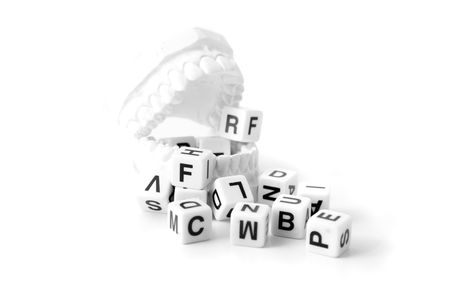 A plaster cast of teeth with a lot of dices showing different letters. All on white background.