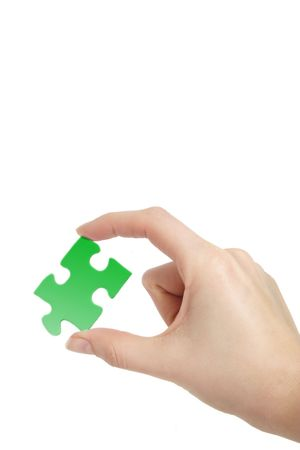 conceptions: A person holding a green piece of a puzzle in his hand. All on white background.