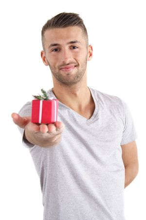 A handsome man handovers a small present. All isolated on white background. photo