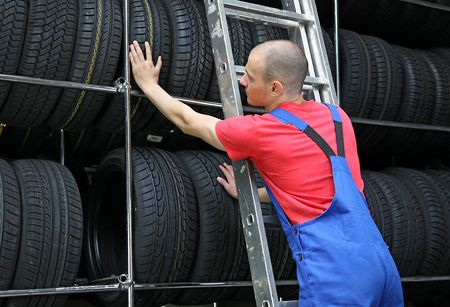 auto garage: A motivated worker in a tire workshop standing on a ladder and checking the stock Stock Photo