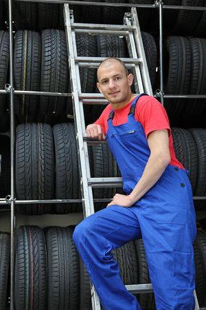 A motivated worker in a tire workshop standing on a ladder. photo