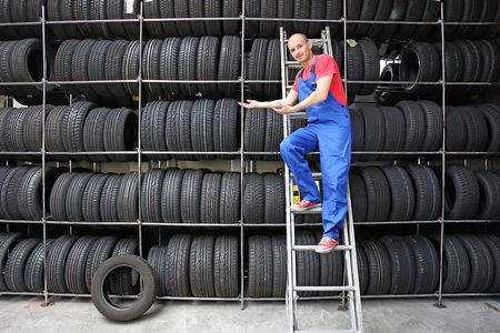 A trustful worker standing on a ladder presenting the tire rack. photo