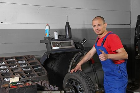 A working mechanist in a tire workshop. Stock Photo