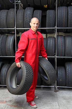 stocktaking: A motivated worker in a tire workshop carrying two tires.
