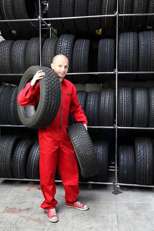 mechanist: A motivated worker in a tire workshop carrying two tires.