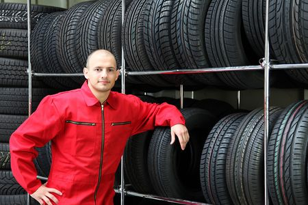mechanist: An optimistic mechanist standing next to a rack full of tires. Stock Photo