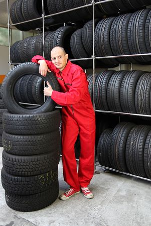 mechanist: An optimistic mechanist standing next to pile of tires. Stock Photo