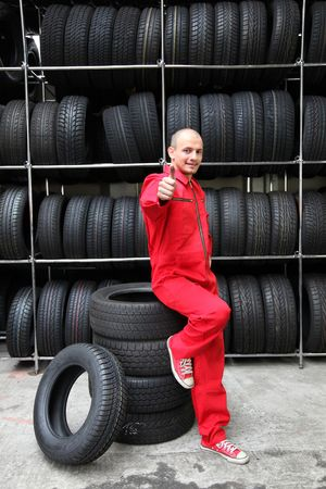 mechanist: A positive mechanic in a garage standing next to a rack full of tires and making a positive gesture. Stock Photo