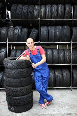 An optimistic mechanic standing in front of a rack full of tires. photo