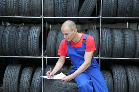 mechanist: A worker takes inventory in a tire workshop and checks the stock. Stock Photo