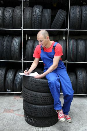 mechanist: A worker takes inventory in a tire workshop.