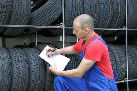 warehouseman: A worker takes inventory in a tire workshop and checks the stock. Stock Photo