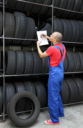 stock car: A worker takes inventory in a tire workshop and checks the stock. Stock Photo
