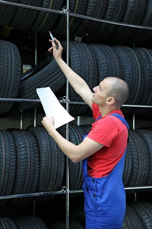 stocktaking: A worker takes inventory in a tire workshop and checks the stock. Stock Photo