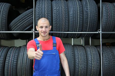 mechanist: An optimistic mechanist standing in front of a rack full of tires.