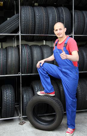 A smiling mechanic in a garage standing next to a rack full of tires and making a positive gesture. photo